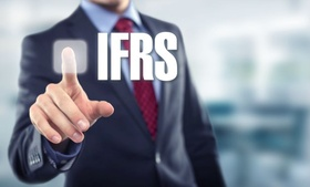 Mann im Anzug zeigt auf Schriftzug IFRS