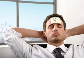 Mann im Buero, nachdenklich mit Haenden im Nacken, Fragezeichen auf Stirn