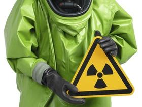 Mann im gruenen Schutzanzug haelt Radioaktiv-Schild