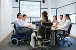 Mann im Rollstuhl sitzt mit Kollegen an Besprechungstisch