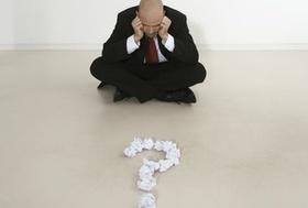 Mann im Schneidersitz hat Fragezeichen aus Papierballen vor sich