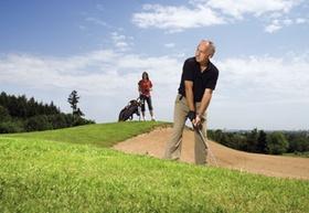 Aelterer Mann auf Golfplatz an Sandbunker, junge Fau mit Caddy im Hgr.