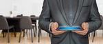Mann in Anzug mit Tablet vor leerem Konferenzraum
