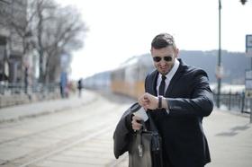 Mann in Anzug schaut fluchend auf seine Uhr