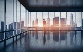 Mann steht in scheinbar leerem Raum vor Glasfenster und schaut auf Hochhäuser