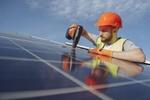 Mann installiert Photovoltaik auf Dach, Solarstrom