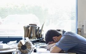 Mann legt Kopf auf überfüllten Schreibtisch