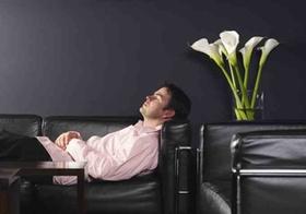 Mann liegt entspannt auf schwarzem Sofa
