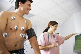 Mann macht EKG, Krankenschwester steht daneben