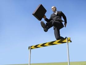Mann mit Aktenkoffer springt über Hürde