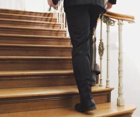 Mann mit Aktentasche geht Holztreppe hinauf