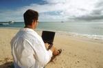Mann mit Anzug und Laptop und sitzt am Starnd uns blickt aufs Meer