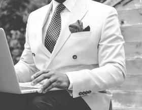 Mann mit Anzug vor Laptop