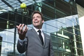 Mann mit Anzug wirft Apfel in die Luft