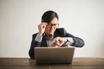 Mann mit Brille schaut verduzt auf seine Uhr