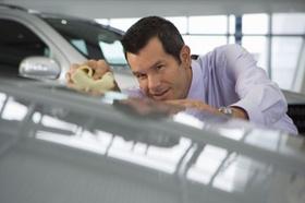 Mann mit Hemd poliert Auto