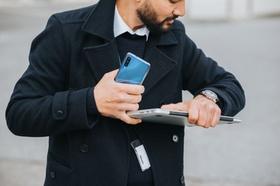 Mann mit Laptop und Handy schaut auf seine Uhr