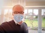 Mann mit Maske in Wohnung
