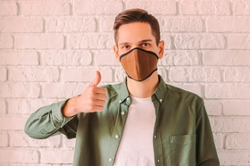 Young stylish hipster in protective mask on face show thumb up gesture. Prevention of coronavirus CO