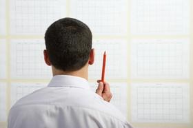Mann mit Stift planend vor Tafel mit Papieren