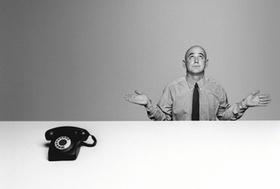 Mann neben Telefon schaut ratlos oder fragend