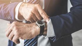 Mann schaut auf Armbanduhr
