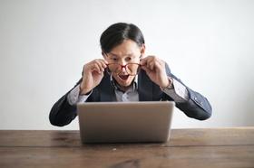 Mann schaut durch Brille auf Laptop