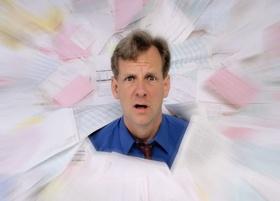 Mann schaut erschreckt gestresst aus Papierstapel