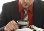 Junger Geschäftsmann an seinem Arbeitsplatz liest mit einer Lupe in Akten (Model: Kosta Lales)
