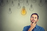 Portrait thinking handsome man looking up with idea light bulb above head isolated on gray wall back