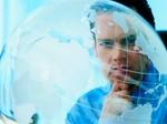 Mann schaut nachdenklich auf transparenten Globus
