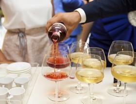 Mann schenkt Wein in Gläser ein