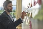 Mann schreibt Ideen auf Wand mit Klebezetteln