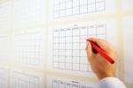 Mann schreibt Termin in Kalender an der Wand