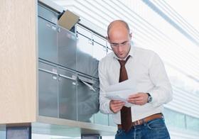Mann sieht sich seine Post am Briefkasten an
