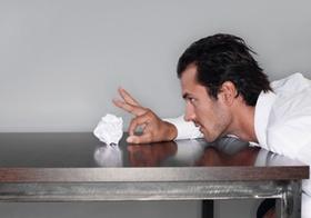Mann sitzt an Tisch, schiesst mit Papierkugel