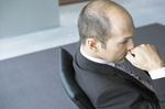 Mann sitzt an Tisch und hält seine Faust vor den Mund