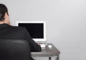 Mann sitzt an Tisch vor Computerbildschirm