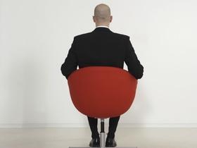 Mann sitzt auf Stuhl Rücken zum Betrachter gedreht