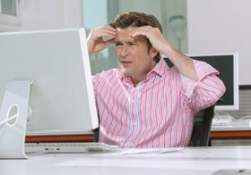 Mann sitzt im Buero gestresst vor Computer