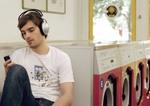 Mann sitzt im Waschsalon, hoert Musik