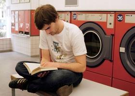 Mann sitzt im Waschsalon, liest ein Buch