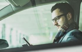 Mann sitzt in Auto und blickt auf Smartphone