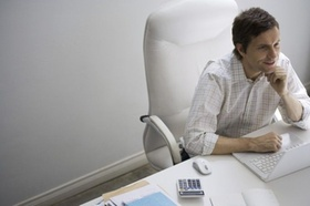 Mann sitzt lächelnd vor Laptop Maus Taschenrechner