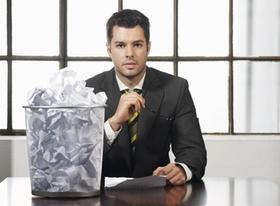 Mann sitzt mit vollem Papierkorb an Schreibtisch