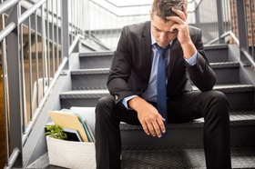 Mann sitzt nach Kündigung verzweifelt auf Treppe