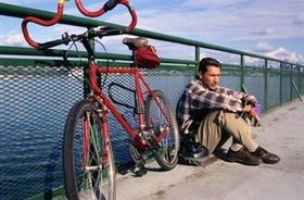 Mann sitzt neben Fahrrad am Fluss