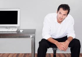 Mann sitzt neben Tisch mit Computerbildschirm