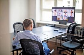 Mann sitzt vor virtuellem Teammeeting