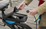 Mann steckt Ladekabel in Elektrofahrrad
